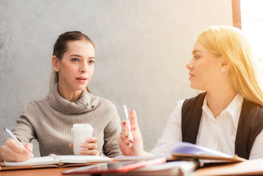 Two female students sit at desk discussing jobs in betting industry.